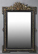 French Ebonized, Gilt and Gesso Louis XVI Style Overmantel Mirror, c. 1870, with a central crest of a floral basket and musical inst...