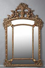 Louis XV Style Copper Gilt Composition Overmantel Cushion Mirror, 20th c., the pierced floral urn crest over putto decoration and a...