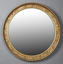 American Aesthetic Style Circular Gilt and Gesso Mirror, early 20th c., with a concave relief grape and relief rim around a wide bev...