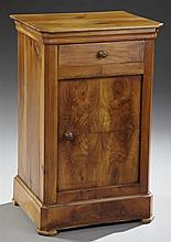 Louis Philippe Carved Walnut Nightstand, late 19th c., the canted edge top over a single frieze drawer above a bookmatched figured w...