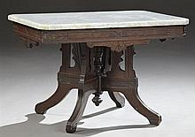 Victorian Eastlake Carved Mahogany Marble Top Center Table, c. 1900, the figured canted corner white marble top over an incised carv...