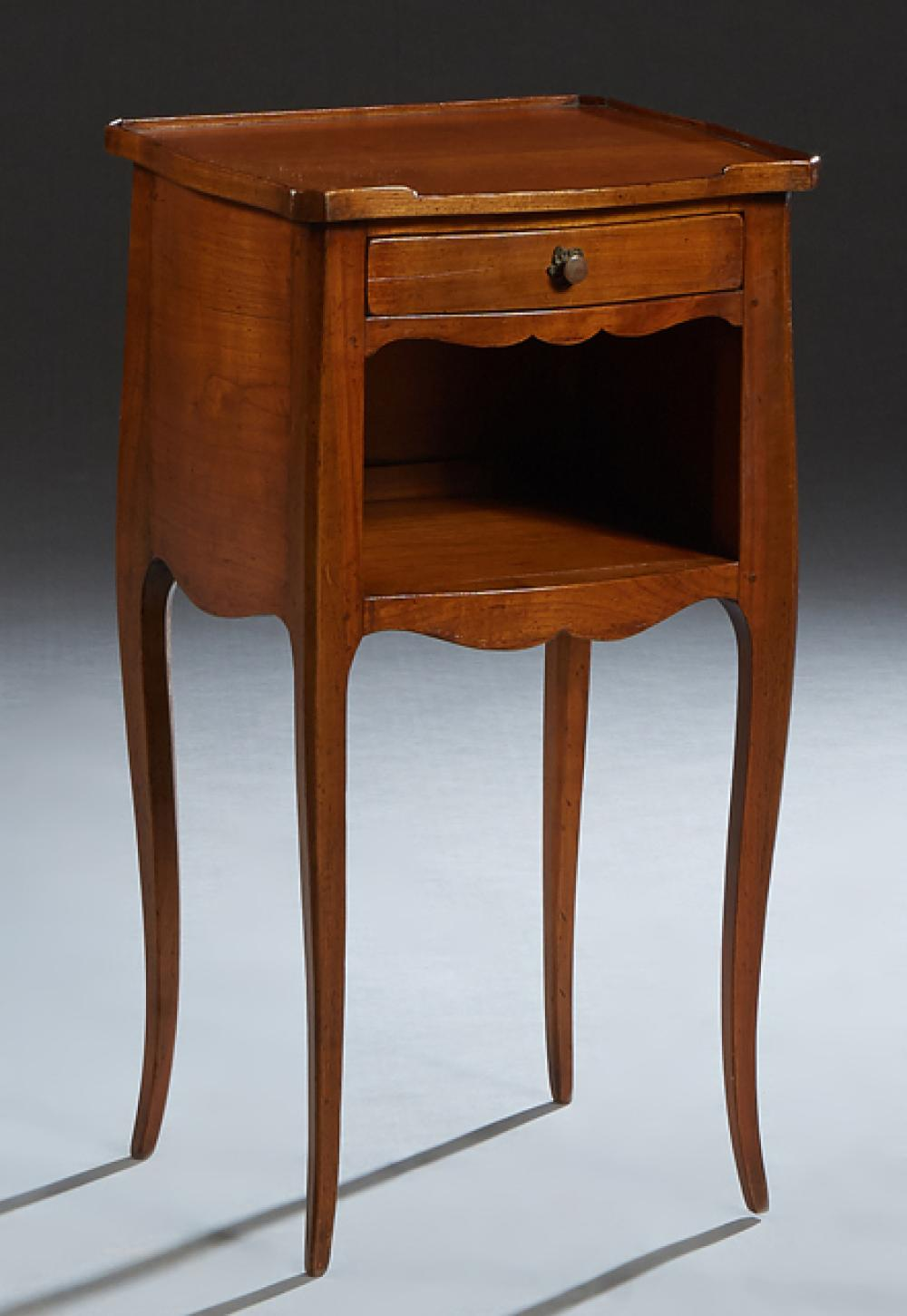 French Louis XV Style Carved Cherry Bowfront Nightstand, 20th c, the 3/4 galleried top over a frieze drawer and open storage, on squ...