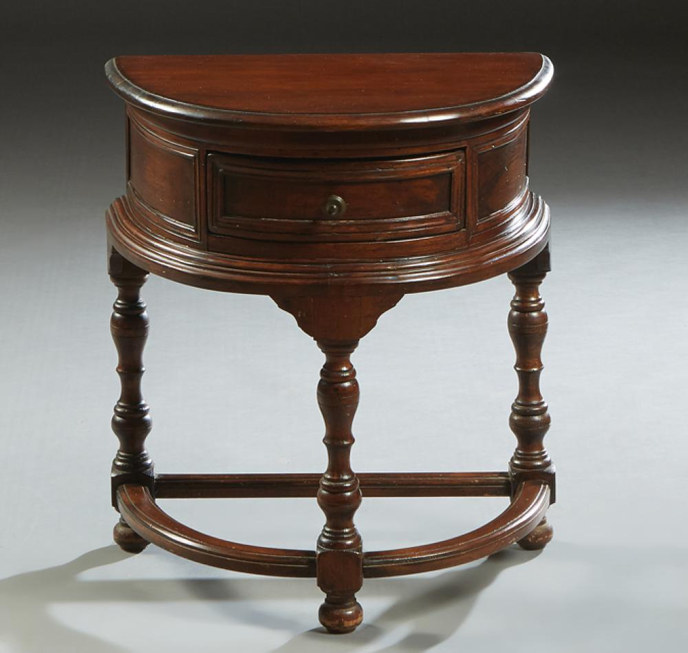French Louis XIV Style Carved Walnut Nightstand, 20th c., of demilune form with a center frieze drawer, on three turned legs joined...