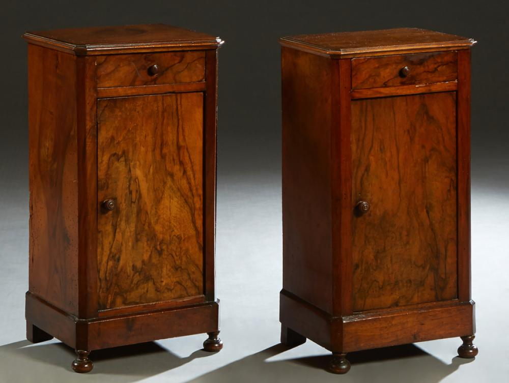 Pair of Louis Philippe Carved Walnut Nightstands, 19th c., the stepped canted corner top over a frieze drawer above a long cupboard...