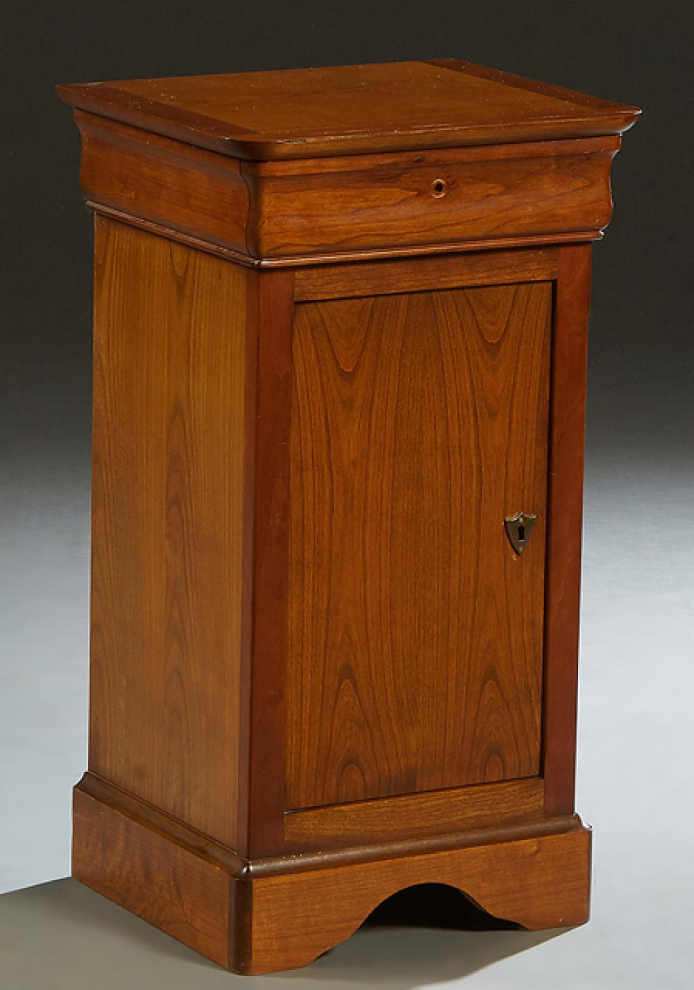 French Louis Philippe Carved Cherry Nightstand, 20th c., the rounded corner top over a frieze drawer and a long cupboard door, on a ...