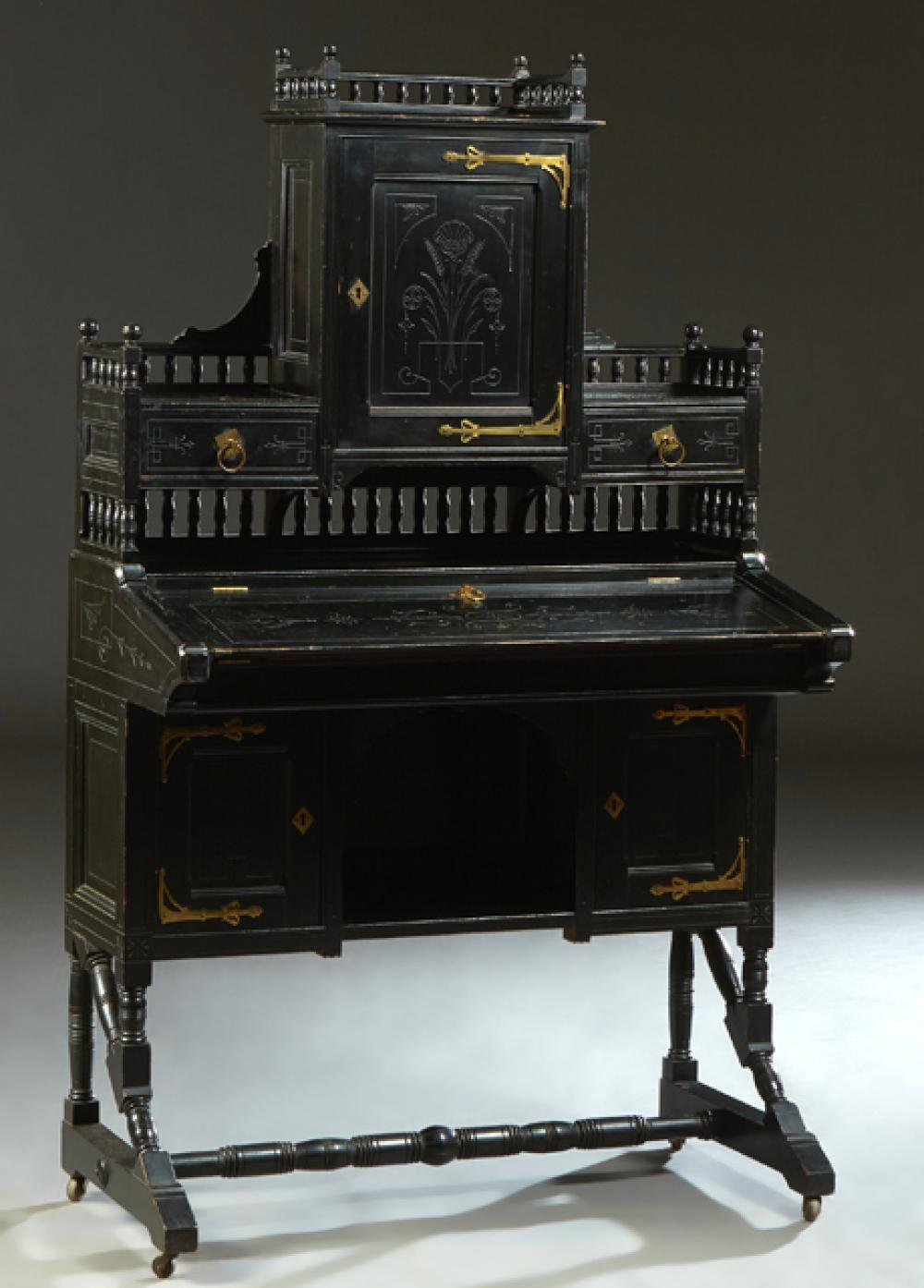American Aesthetic Ebonized Cherry Brass Mounted Secretary Desk, c. 1880, with a central spindled gallery incised cupboard, flanked ...