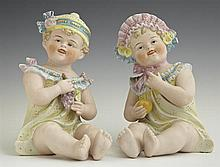 Pair of German Polychromed Bisque Piano Babies, late 19th c., one holding an apple, the other holding grapes, H.- 7 1/2 in., W.- 5 1...