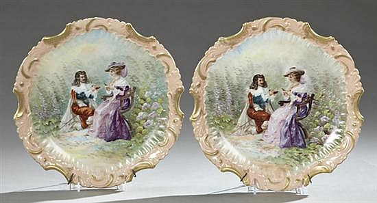 Pair of Hand Painted Porcelain Chargers, c. 1890, with scalloped gilt and relief decorated borders with central reserves of lovers i...