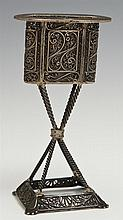 Unusual Sterling Table Top Match Holder, early 20th c., Israel, the basket top with pierced swirled decoration, on an X-form support...
