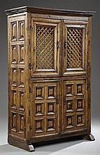 Spanish Carved Oak Armoire, c. 1800, the stepped ogee crown over latticed double doors above double doors, each with six raised pane...