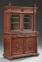 French Jacobean Style Carved Oak Buffet a Deux Corps, 19th c., the broken arch crown above double setback glazed doors flanked by ba...