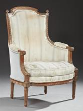 Louis XVI Style Carved Walnut Upholstered Bergere, 20th c., the arched crown flanked by finials above an upholstered arched high bac...