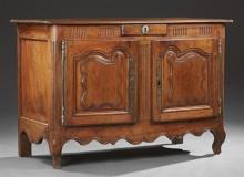 French Provincial Louis XV Style Carved Walnut Sideboard, mid 19th c., the ogee edge rounded corner top over a central frieze drawer...