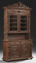 French Henri II Carved Oak Buffet a Deux Corps, 19th c., the stepped carved crown above double glazed doors flanked by high relief g...