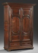 Louis XVI Style Carved Walnut Armoire, early 19th c., the stepped ogee crown above double triple fielded panel doors with long iron...