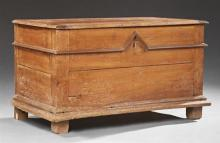French Provincial Carved Cherry Coffer, early 19th c., the rounded edge lid over a base with applied stepped molding on a sloping st...