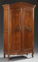 Diminutive French Carved Walnut Armoire, 19th c., the stepped arched top over arched panel double doors with iron fiche hinges and e...
