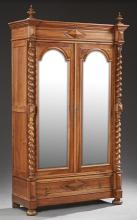 French Henri II Style Carved Walnut Armoire, c. 1880, the stepped break front finialed crown over setback arched wide beveled mirror...