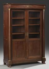 French Empire Style Carved Mahogany Ormolu Mounted Bookcase, 19th c., the rectangular crown over setback double doors with glazed up...