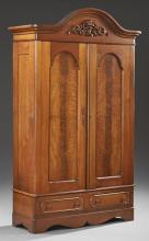 American Victorian Carved Walnut Armoire, 19th c., the stepped arched top over arched double doors, on a base with two drawers on a...
