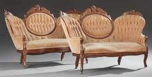 Pair of Victorian Carved Walnut Triple Back Settees, 19th c., the serpentine crests with burled wood panels above tufted backs and a...