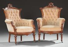 Pair of American Victorian Carved Walnut Armchairs, 19th c., the crest rail with a central carved medallion above a tufted back and...