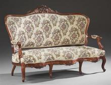 American Carved Walnut Sofa, 19th c., the arched curved upholstery back with a floral and leaf crest to upholstered arms, over a ser...