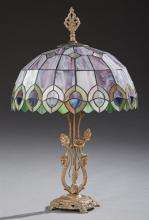Tiffany Style Slag Glass Table Lamp, late 20th c., the leaded domed slag glass shade on a gilt bronze base with two dragon supports,...
