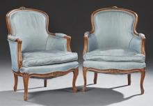 Pair of French Carved Bergeres, 20th c., the floral carved crest rails over upholstered arms and a bowed cushion seat, on cabriole l...