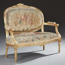 Louis XVI Style Gilt Settee, 19th c., the crest above an upholstered medallion back and bowed seat flanked by upholstered arms, on t...