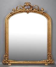 American Victorian Gilt and Gesso Overmantle Mirror, c. 1870, possibly by L. Uter, New Orleans, the arched frame with a pierced leaf...