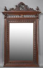 French Carved Oak Henri II Style Overmantle Mirror, late 19th c., Brittany, the arched spindled wheel form crest over a stepped crow...
