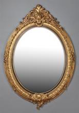 Louis XV Style Oval Gilt Overmantle Mirror, 20th c., with a leaf form crest over a beveled plate within a ribbed frame, the bottom w...
