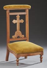 French Carved Walnut Prie Dieu, 19th c., the upholstered armrest over a cross backsplat, to a bowed seat on turned legs, with olive...