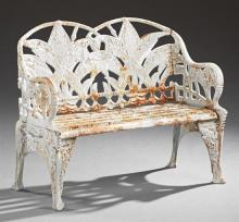 Aesthetic Style White Cast Iron Garden Bench, 20th c., the pierced double arched leaf relief back over a slatted seat and scrolled r...
