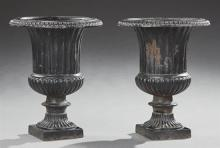 Pair of Cast Iron Campana Form Garden Urns, 20th c., the everted relief urns over ribbed sides to a socle supports on a square base,...