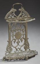 French Cast Iron Umbrella Stand, c. 1870, the arched top on a pierced scrolled back, issuing an umbrella holder over a dished base o...