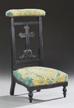 French Ebonized Beech Prie Dieu, 19th c., the upholstered arm rest, over a cross backsplat, to a bowed seat, on turned legs, now in...