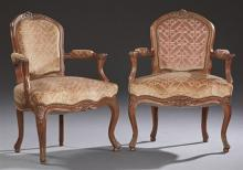 Pair of French Carved Walnut Louis XV Style Upholstered Fauteuils, early 20th c., the arched floral carved crest rails over shield b...