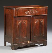 American Carved Mahogany Washstand Base, 19th c., the serpentine top over a frieze drawer above two Gothic arched cupboard doors, on...