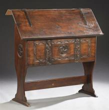 Unusual French Carved Oak Church Lectern, 19th c., the slanted top with strap hinges over a side with figural carved pilasters, on s...