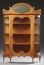 American Victorian Carved Oak Curved Glass Cabinet, c. 1900, the oval beveled mirror back over a stepped top above a glazed door fla...