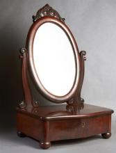 American Carved Mahogany Shaving Mirror, late 19th c., the oval mirror with a scrolled surmount, on curved reeded supports to a bowe...