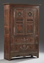 French Provincial Carved Oak Armoire, 19th c., Brittany, the stepped crown over double fielded panel doors with spindled wheels over...
