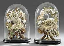 Pair of Blown Glass Wedding Domes, 19th c., the cushions mounted with silk flowers, on ebonized bases, Domes- H.- 19 in., W.- 13 in....