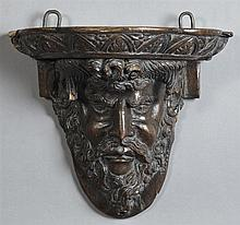 Figural Carved Wooden Bracket Shelf, 18th c., the shaped shelf on a support with a relief carved bust of Bacchus, H.- 12 1/4 in., W....