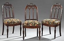 Set of Three Gothic Revival Carved Mahogany Dining Chairs, early 20th c., with a pierced carved acanthus handle, to a pierced trefoi...