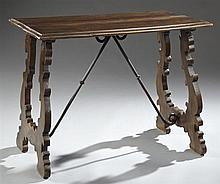Spanish Style Carved Beech and Wrought Iron Table, late 19th c., the two board top with bullnose edge, supported on a pierced lyre f...