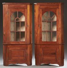 Pair of American Carved Cherry Corner Cabinets, 20th c., the canted corner stepped crown over an astragal glazed door above a cupboa...