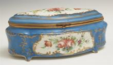 A Sevres Style Porcelain Dresser Box, 19th c., of shaped oval form with domed lid and gilt bronze mounts, having hand painted floral...
